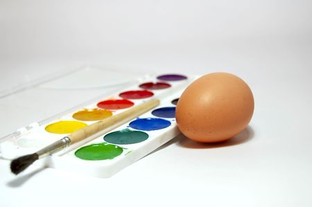 set of the paints and egg on background. Brush on foregrounds photo
