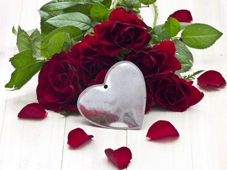 On a wooden tray recumbent red rose with rose sheets photo