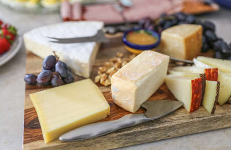 Assorted Cheese plate spread with blueberries, honey and  strawberries. Stock fotó