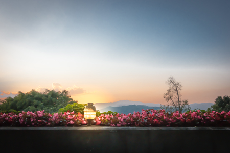Sunset on the garden terrace. There is a lamp to light the night. Imagens