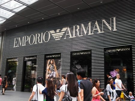 materialism: outside Mandarin Gallery mall at Orchard Road in Singapore, February 27, 2011 - shoppers walking along a pavement in front of an Emporio Armani display