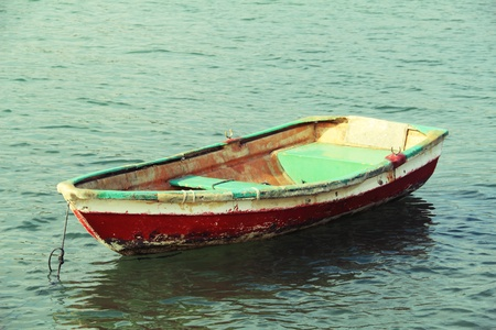 fishing village: unoccupied solitary colorful boat floating in water