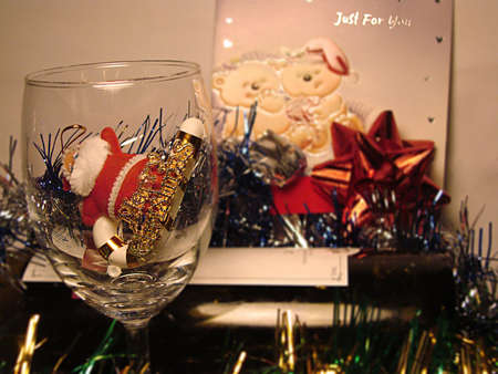 emulate: Merry Christmas: Santa in a wine glass. Picture tken in a low lit room to emulate a warm Christmas evening scene. Camera was focused on the wine glass andthe image was edited blur the background further.