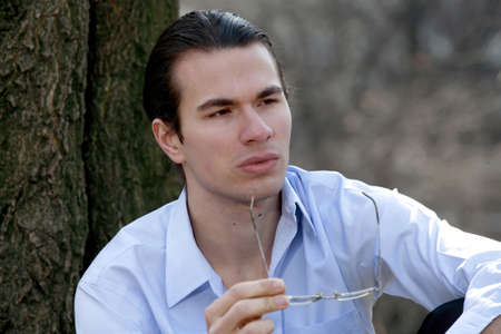 deep in thought: Male sitting outdoors in deep thought.  Stock Photo