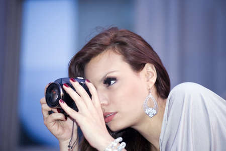 early twenties:  latin woman in her early twenties with camera.  She is from Bolivia and was photographed July, 2009 in the USA.  Stock Photo