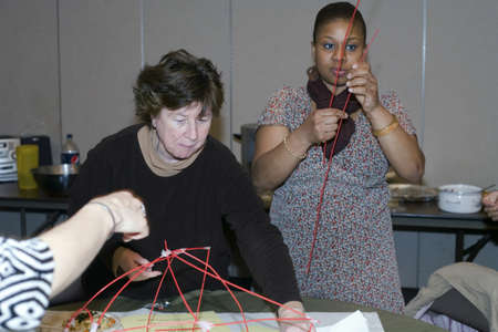 believers: Several Christian believers participate in a game held during the Trinity Baptist Church fellowship dinner.  Shown here the members compete  against another table of Christians on who can build the highest tower within a specific amount of time.  The chur