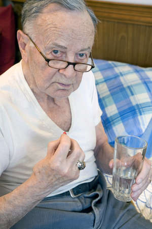 semite: Senior citizen takes medication with water just before bedtime.      Stock Photo