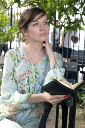 Russian girl sits in the park and reads her Russian Bible.  She was in her late twenties at the time of shoot. Photographed May, 2009 in New York, USA. Model: Irina Nikolskaya.  Release number 12