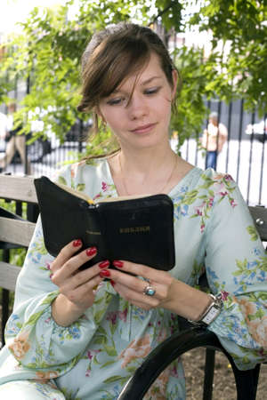 late twenties: Russian girl sits in the park and reads her Russian Bible.  She was in her late twenties at the time of shoot. Photographed May, 2009 in New York, USA. Model: Irina Nikolskaya.  Release number 12