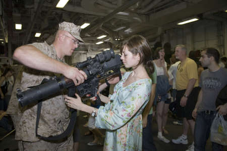 New York, NY - May 23: United States Marine assists a civilian holding an M224 weapon.  Photographed during Fleet Week aboard the USS Iwo Jima May 23, 2009 in NYC.