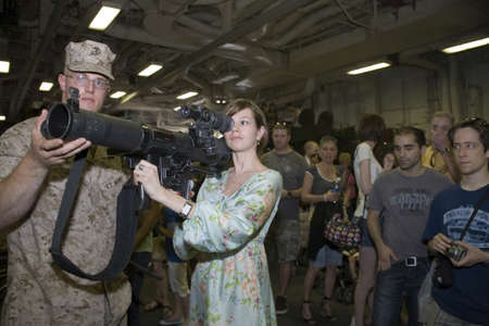 civilian: New York, NY - May 23: United States Marinehelps civilian with an M224 weapon.  Photographed during Fleet Week aboard the USS Iwo Jima May 23, 2009 in NYC.