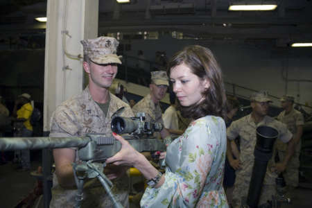 Civilian Irina gets acquainted with the M40A3 Sniper Rifle with the the help of a United States Marine.  The M40A3 Sniper rifle is a shoulder fired, bolt action, scoped sniper rifle.  Photographed during the 2009 Fleet Week in NYC aboard the USS Iwo Jima  Stock Photo - 9286615