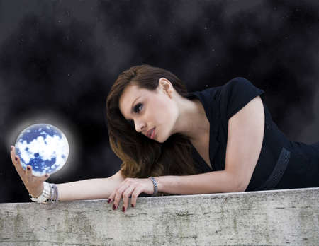 early twenties:  latin woman in her early twenties with planet.  She is from Bolivia and was photographed outdoors in New York City.  Image taken July, 2009 in the USA.   Stock Photo