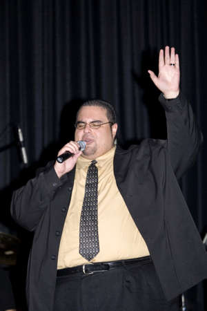 BRONX, NEW YORK - APRIL 9: Pentecostal Christian singer Hector Bonano sings during event held at Lehman High School. Taken April 9, 2011 in the County of the Bronx, NY. Editorial
