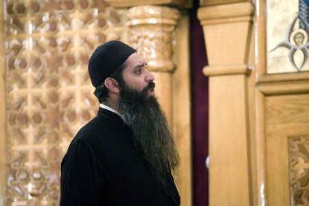 vespers: A Coptic Orthodox Priest prays during the Saturday Vespers prayer service inside the Coptic Orthodox Church of St George in Brooklyn NY, September 2009 in the USA.