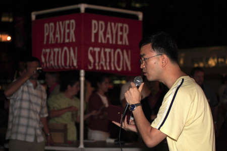 testify: New York, NY - August 23: A Korean friend shown here assists Rev. Shawn Holes during open air preaching on Union Square.  Taken August 23rd, 2008 in New York City.