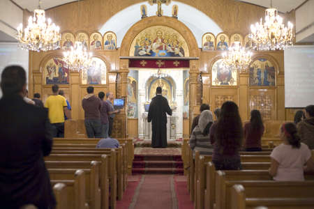 A Church priest blesses with the cross during Vespers prayer night at the Coptic Orthodox Church of St George in Brooklyn NY. Photographed September 2009 in the USA.   Editoriali