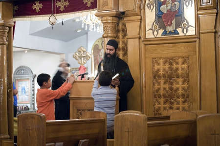 A church priest guides parishoners during Vespers prayer night at the Coptic Orthodox Church of St George in Brooklyn NY. Photographed September 2009 in the USA.   新聞圖片