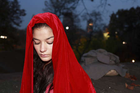 A young girl wearing a red robe in park. Stock fotó