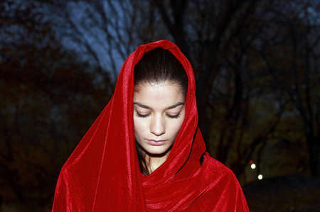 A young girl wearing a red robe in park. Stock Photo - 10315451