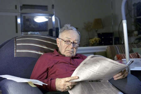 Senior reading paper .  He is Romanian born and  Jewish.  He is 85 years old.     photo