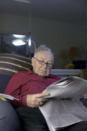 Senior reading paper  on sofa.  He is Romanian born and  Jewish.  He is 85 years old.    Stock Photo - 10314823