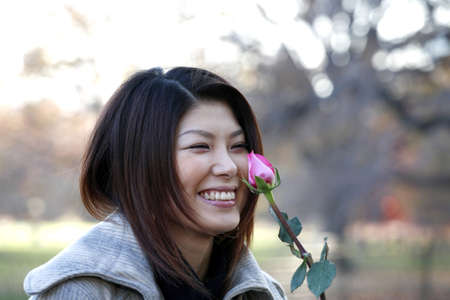 japanese ethnicity: Asian girl with rose outdoors on a fall day.  She is of Japanese ethnicity and was 23 at the time of shoot.