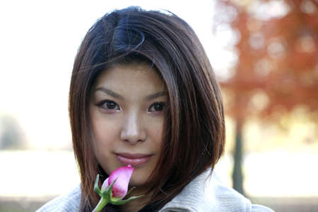 japanese ethnicity: Asian girl with roses outdoors on a fall day.  She is of Japanese ethnicity and was 23 at the time of shoot.