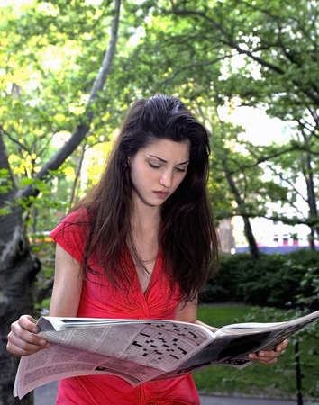 Girl reads newspaper in park.   Photographed June, 2007 in Central Park New York in the USA.  She was in her twenties at the time of shoot and is Jewish American.           Stock Photo