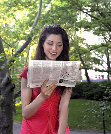 Girl reads newspaper in park.   Photographed June, 2007 in Central Park New York in the USA.  She was in her twenties at the time of shoot and is Jewish American. Stock Photo - 10328823