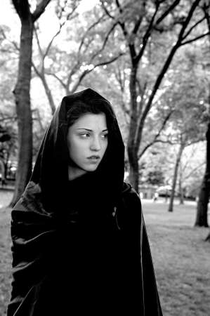 Girl wearing cloak in park.  She is Jewish American and was in her twenties at the time of shoot.  Photographed June, 2007 in Central Park, New York, USA.