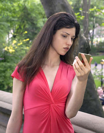 Girl checks her makeup while visiting Central Park in New York City.  Photographed June, 2007 in the USA.  She was in her twenties at the time of shoot and Jewish American.        photo