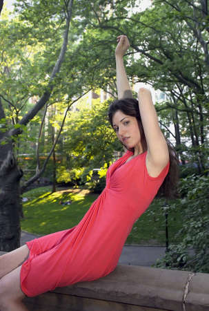 Girl stretching as she sits in Central Park New York.   She was in her early twenties at the time of shoot and Jewish American.      Photographed June, 2007 in the USA.             photo