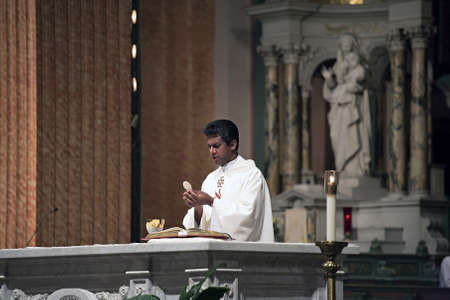 NEW YORK, NY - AUGUST 08: A priest performs the eucharistic liturgy at Saint Jean Baptiste Church.  Photographed August 08, 2008 in New York City.
