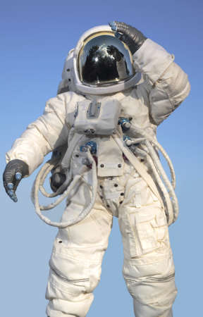 Astronaut wearing a pressure suit and saluting.
