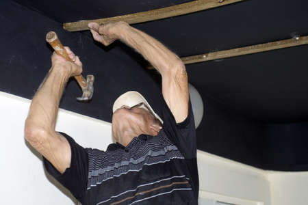An active senior man hammers nail into ceiling.  His ethnicity is Puerto Rican. photo