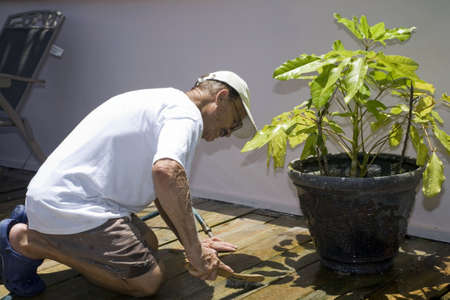 A senior man cleaning his outdoor deck.  He is of Puerto Rican ethnicity. photo