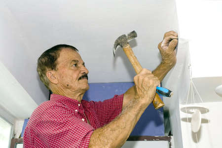 A senior man hammers nail into wall.  He is of Puerto Rican ethnicity. photo