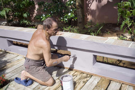 A senior man paints outdoors.  He is of Puerto Rican ethnicity. photo