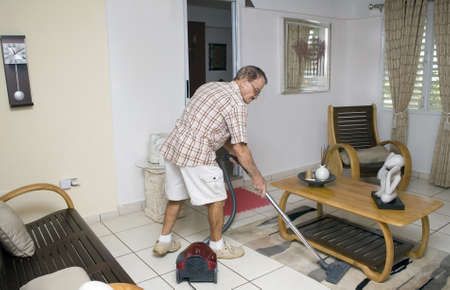 A senior man vacuums his living room.  He is of Puerto Rican ethnicity. Stock Photo