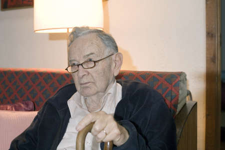A senior man sitting and holding his cane.