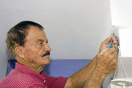 A senior man uses a screwdriver to screw in a small screw into a wall. photo