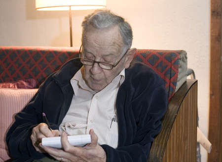 A senior man sits and writes on a pad. Stock Photo - 11071966