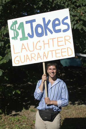 NEW YORK, NY - JULY 9: A man holds a sign offering jokes for a dollar a laugh while in Central Park.  Photographed July 9, 2011 in New York City.