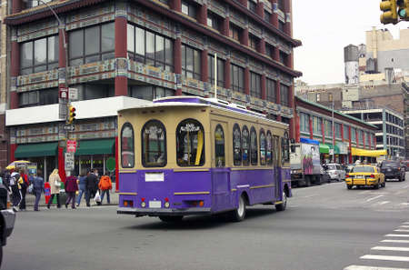 A trolley car rides downtown Chinatown street in New York City.