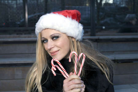 A Caucasian woman holding candy canes and wearing a Santa hat. photo