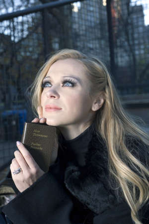 gods: Caucasian woman holding a small Bible while outdoors  Stock Photo