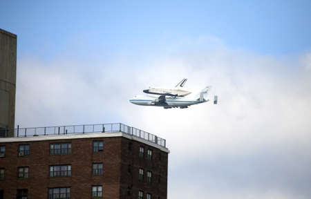 reuseable: NEW YORK, NY - April 27:  The Space Shuttle Enterprise near a Harlem building as it flies over Manhattan while seated atop a 747 aircraft.  Photographed April 27, 2012 in NYC.