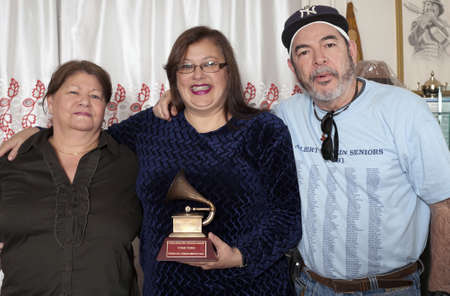 BRONX, NEW YORK - DECEMBER 23: Yomo Toros brother Angel, Yomos wife Minerva center and Angels wife left, unite to  remember international cuatro player Yomo Toro who was awarded the Latin Grammy but passed away before he could accept it. Taken December Editorial