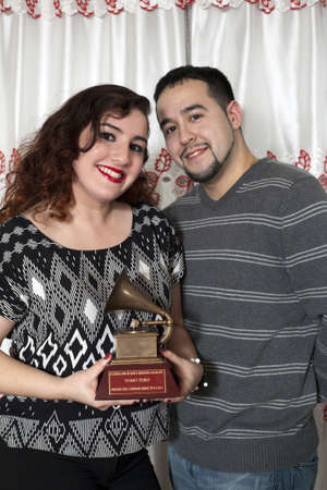 BRONX, NEW YORK - DECEMBER 23: Yomo Toros niece Christina and her boyfriend hold  Latin Grammy to remember  international cuatro player Yomo Toro who was awarded the Grammy but passed away before he could accept it. Taken December 23, 2012 in the Bronx,